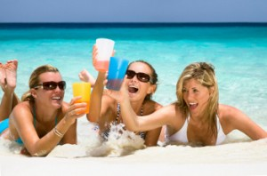 Three young women on beach for spring break and drinking