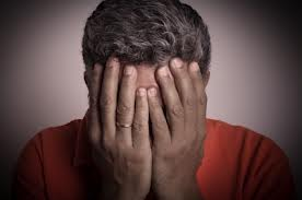 A man hides his face with shame-related behavior during addiction recovery before he relapses.